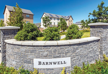 Stone wall showing plaque from Barnwell Estate. Blue sky, leafy planting and houses can be seen in the background