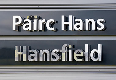 Roadside view of Hansfield Golf Club's main sign. The golf course can be seen in the background.